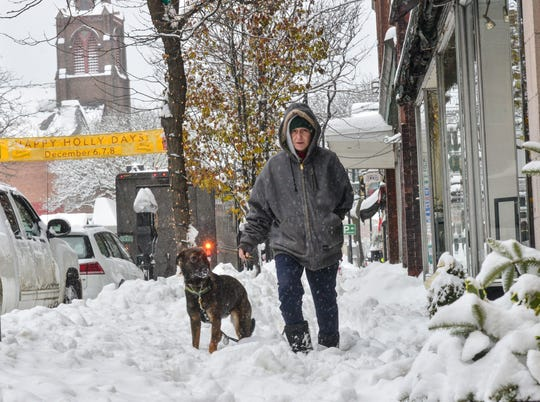 Anne Cummingham walks her dog, Gracie, through the snow on Main Street in Brattleboro. Vt., Monday, Dec. 2, 2019. A final wallop of a seemingly endless winter storm that impacted most of the country over the long holiday weekend is bearing down on the East.