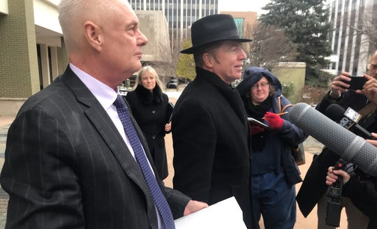 Rep. Larry Inman, left, stands with reporters and his attorney, Chris Cooke, outside federal court in  Grand Rapids after the first day of his trial on Tuesday, Dec. 3, 2019.