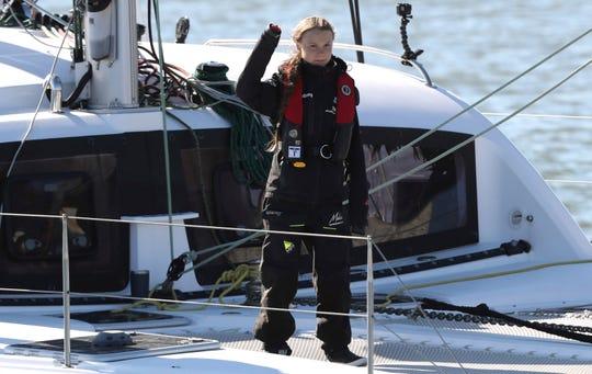 Climate activist Greta Thunberg waves as she arrives in Lisbon aboard the sailboat La Vagabonde Tuesday.