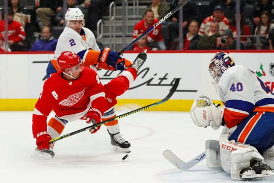 Detroit Red Wings center Dylan Larkin is held by New York Islanders defenseman Nick Leddy in the second period Monday night.