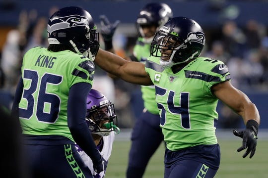 Seattle Seahawks middle linebacker Bobby Wagner, right, reacts with cornerback Akeem King (36) after the Minnesota Vikings failed to convert on a fourth-down play during the second half.