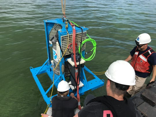 Researchers prepare to drop an environmental sample processor into Lake Erie to measure the severity of algal blooms in July 2019.