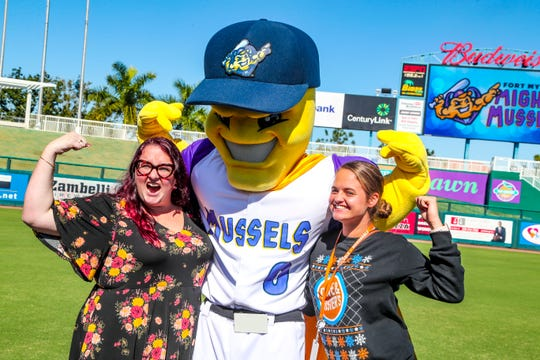"""Hailey O'Quinn (right) and Brigid Purdy (left) pose with the new mascot for the Fort Myers Mighty Mussels. Both women were there for Dave and Busters. The Fort Myers Miracle made a major announcement Tuesday at Hammond Stadium. They will know be named """"Fort Myers Mighty Mussels"""" Officials from the city and county were in hand as well as former players were  there fir the announcement, Monday, December 3, 2019."""