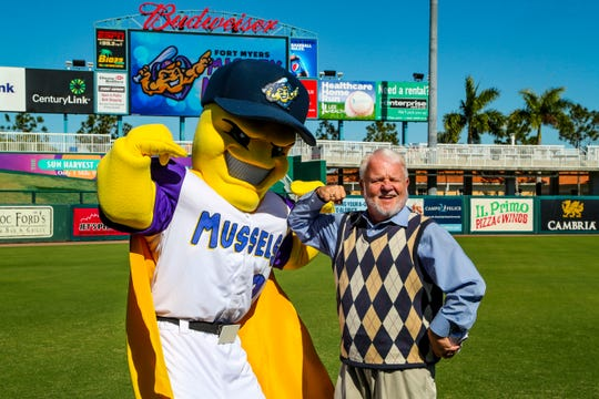 """Gary Israel, fan and National Anthem singer, shows off his muscles with the news team mascot, Mighty Mussels. The Fort Myers Miracle made a major announcement Tuesday at Hammond Stadium. They will know be named """"Fort Myers Mighty Mussels"""" Officials from the city and county were in hand as well as former players were there for the announcement, Monday, December 3, 2019."""