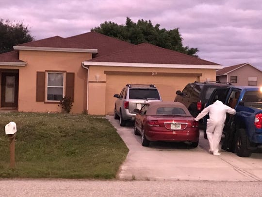 A crime scene cleaning crew member removes his environmental suit at a  house  in the 2600 block of NW 9th Street in Cape Coral where two bodies, a man and a woman, were found Tuesday morning.