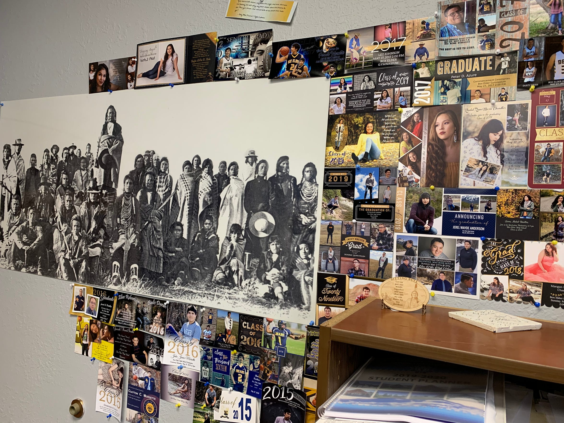 In his office, Superintendent Jeremy MacDonald displays a historical picture of Cree tribal members next to Box Elder students' graduation announcements. The collage reminds MacDonald of the past and how Box Elder students work to shape a better future.