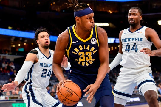 Indiana Pacers center Myles Turner (33) handles the ball against Memphis Grizzlies forward Solomon Hill (44) and guard Dillon Brooks (24)in the first half of an NBA basketball game Monday, Dec. 2, 2019, in Memphis, Tenn.