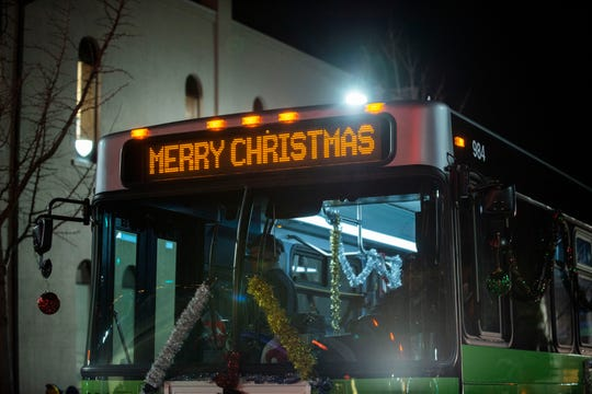A bus shares a holiday message during the Christmas parade in downtown Jackson, Tenn., on Monday, Dec. 2, 2019.