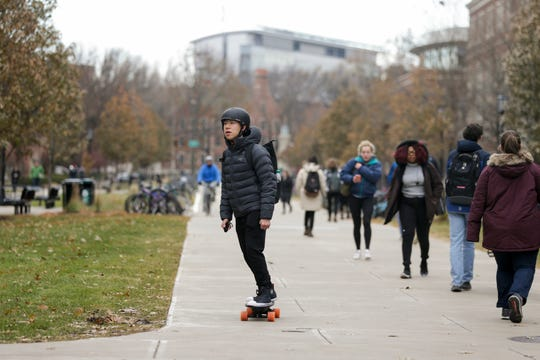 A rider skates across the Engineering mall on an electric skateboard, Tuesday, Dec. 3, 2019 at Purdue University in West Lafayette.
