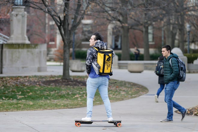 A rider skates near the Engineering Fountain on an electric skateboard, Tuesday, Dec. 3, 2019 at Purdue University in West Lafayette.