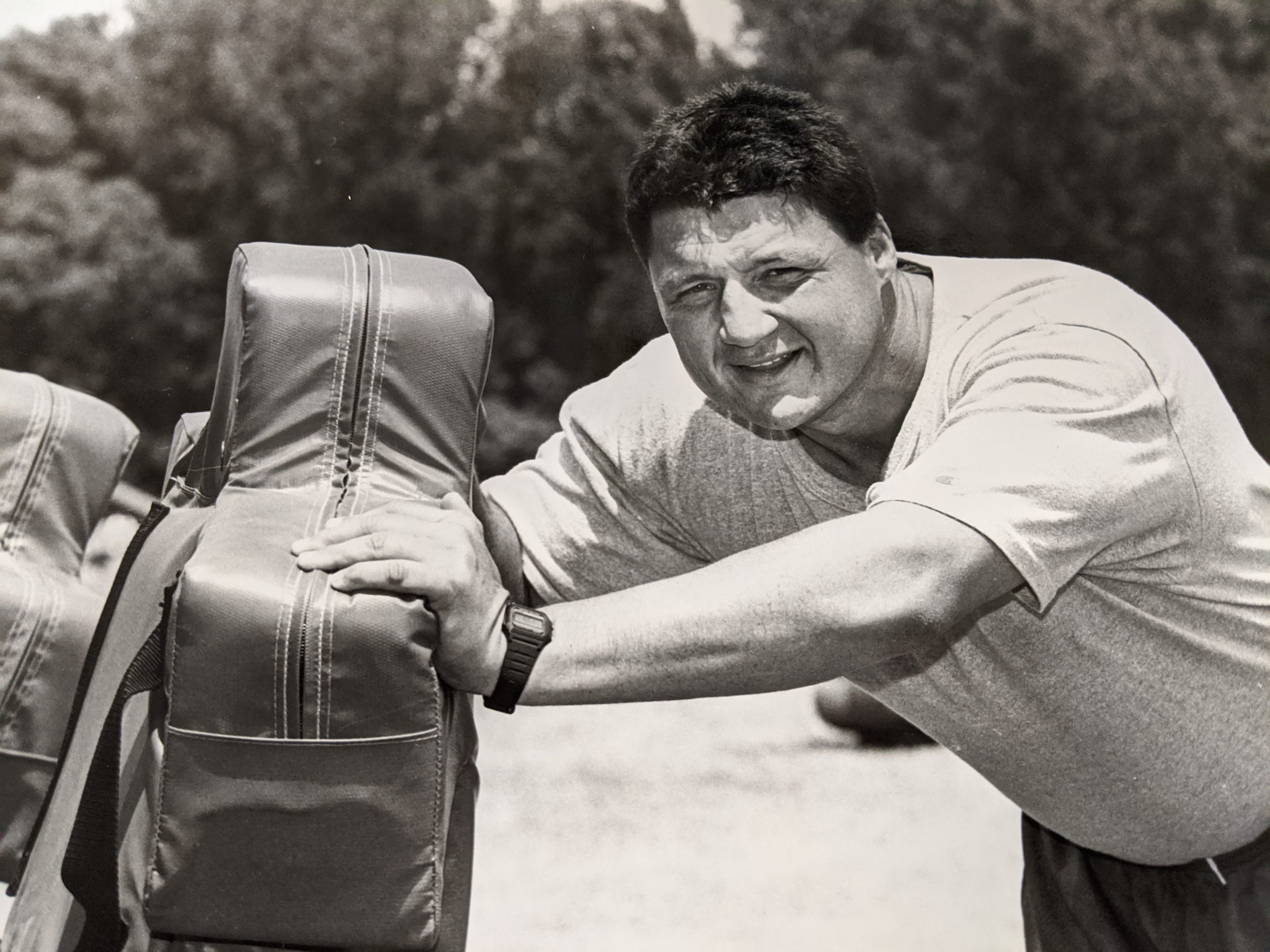 Ed Orgeron's first coaching opportunity at an SEC school came from Arkansas, who paid him $50 a month as their strength coach. Here, Orgeron leans on a tackling dummy at an unknown university practice field.