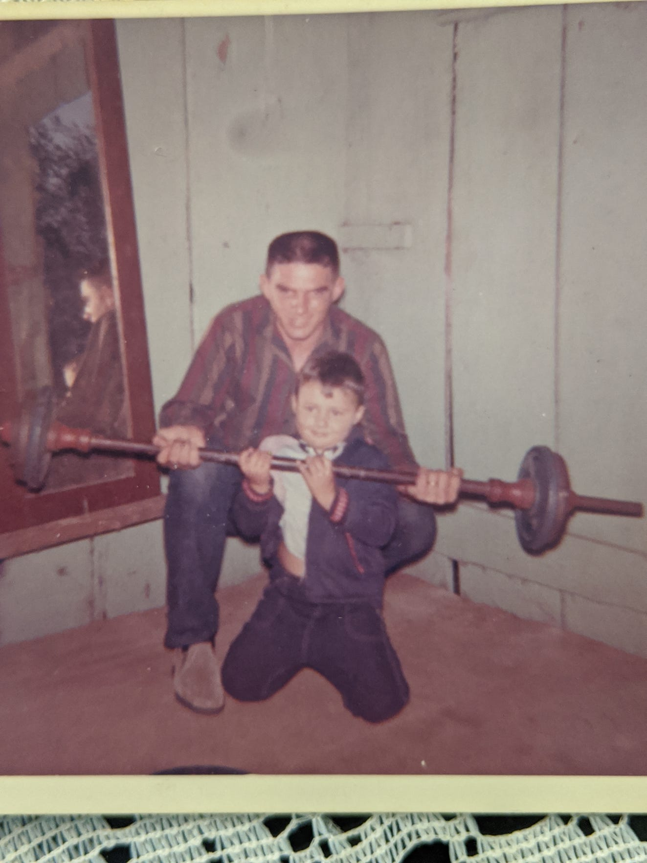 A young Ed Orgeron lifting weights with his father Ed Orgeron Sr.