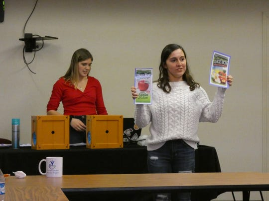 Mindi Klaus, left, a junior at River Valley High School, and Bridget Murphy, right, a senior at Pleasant Local High School, give a presentation about the dangers of vaping at a meeting of Drug Free Marion. Here, Murphy compares the marketing and packaging of a vaping product and a food product.