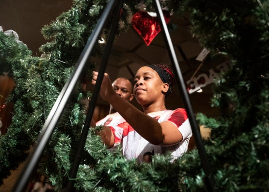 Cecelia Berry hangs an ornament honoring her 12-year-old son Devin Johnson at the 9th annual Season of Remembrance memorial event honoring homicide victims and their families at Memphis City Hall on Monday, Dec. 2, 2019.