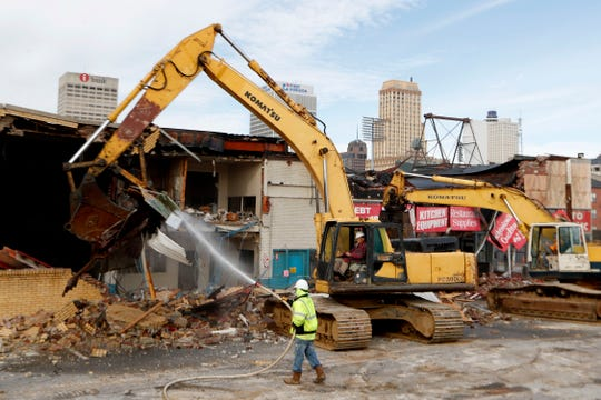 Demolition crews knock down a building Tuesday, Dec. 3, 2019, on Union Row near Danny Thomas Boulevard in Memphis.