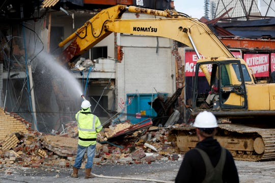 Demolition crews knock down a building Tuesday, Dec. 3, 2019, on Union Row near Danny Thomas Boulevard in Memphis.