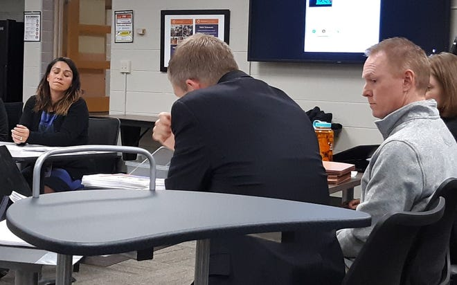 Wauwatosa East softball coach Ed Raue (right), looks at his attorney Mike Huitink while District HR Director Aida Cruz-Farin testifies during a special meeting of the Wauwatosa School Board Dec. 2.