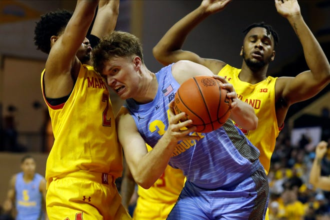 Marquette center Jayce Johnson fights for a rebound against Maryland at the Orlando Invitational.