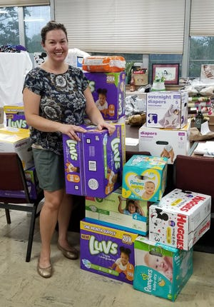 Hope Network Executive Director Liz Beaudoin stands next to boxes of diapers collected ahead of the Mothers Trading Post in October.