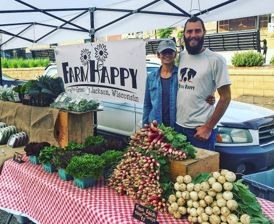 Jennifer Gordon and John McConville sell produce at a farmers market.