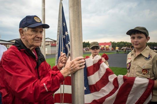World War II veteran Don Jakeway helps raise the American flag before a 2018 game against Licking Valley at Johnstown's Frank H. Chambers Stadium.