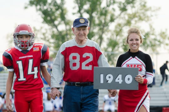 Don Jakeway, center, walks across Johnstown's Frank H. Chambers Stadium field in September of 2015 on Alumni Night with his grandson, freshman Trenton Jakeway, 14, and a Johnstown cheerleader. It was the 75th anniversary of the 1940 team, for which Jakeway played.