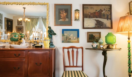 A large mirror over the buffet opens up the dining room. Found art objects, colored glass and pottery, a dining table chair and a vintage pedestal table complement the space.