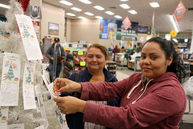 Pictured, from left, are Esperanza Lozoya and Guadalupe Trevizo setting up a Tree of Hope at Peppers Supermarket.