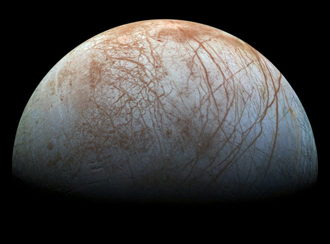 Europa, as seen by the Galileo Spacecraft. Cracks in the ice crisscross the surface. In other regions the ice crust has broken up and refrozen.