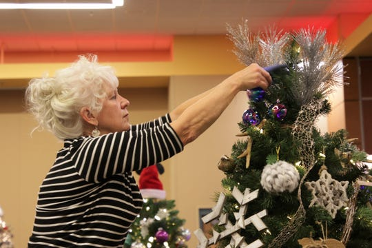 "Karen McPheeters, director of the Farmington Library, adds decorations to her Christmas tree, named ""The North Woods,"" at the Farmignton Civic Center on Dec. 3, 2019. McPheeters made the tree in tribute to her father."