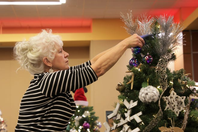 """Karen McPheeters, director of the Farmington Library, adds decorations to her Christmas tree, named """"The North Woods,"""" at the Farmignton Civic Center on Dec. 3, 2019. McPheeters made the tree in tribute to her father."""