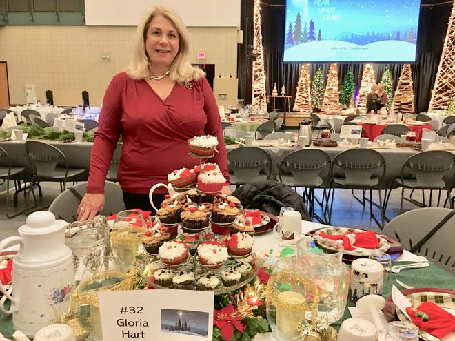 Gloria Hart stands at her beautifully-decorated table at the Advent by Candlelight event at First United Methodist Church. Hart spent a whole day decorating cupcakes with Santa faces, reindeer heads and pandas. She had fun learning about cake decorating.