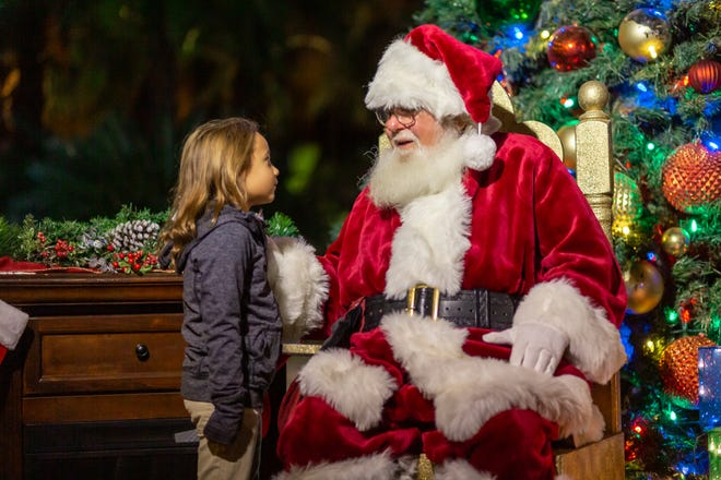A child visits with Santa at WildLights at The Living Zoo and Gardens.