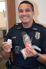 Michael Garcia, an officer with the Pensacola Police Department, shows off the bike lights he and his fellow officers have started passing out to bicyclists who are missing the safety gear.
