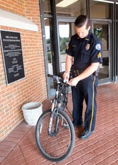 Pensacola Police Department Sgt. Pat Bradley attaches a light to one of the department's bikes on Tuesday. The PPD recently began passing out the free bike lights to bicyclists who are missing the safety gear.