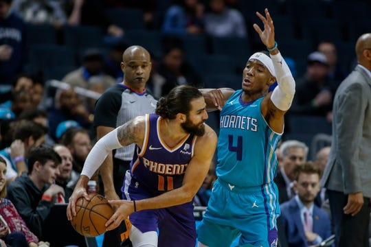 Suns guard Ricky Rubio looks to pass around Hornets guard Devonte' Graham during a game Dec. 2.