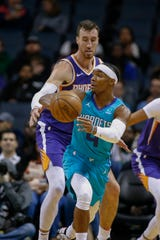 Hornets guard Devonte' Graham passes the ball while being defended by Suns forward Frank Kaminsky III during a game Dec. 2.