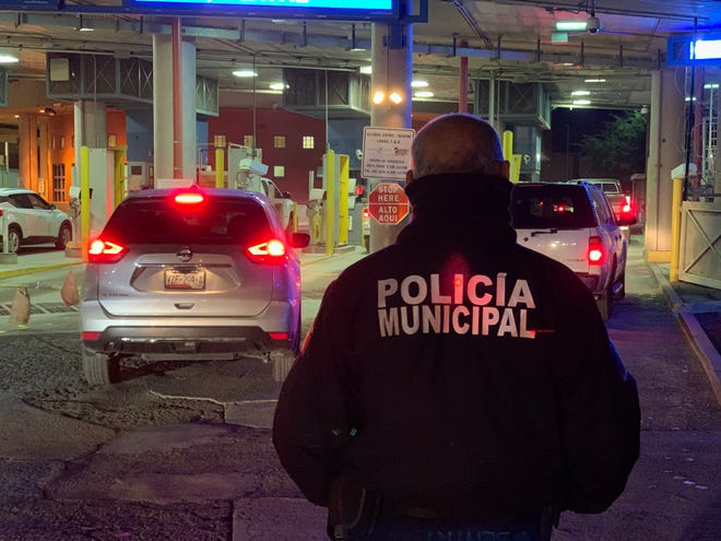 A Nogales police officer stands guard at the vehicle lanes at Nogales' DeConcini port of entry in Nogales on Dec. 2, 2019. The officers were stationed there to prevent migrants from rushing the port of entry.