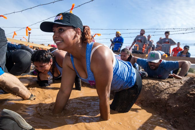 Participants attempt to crawl through a mud pit in a Tough Mudder course