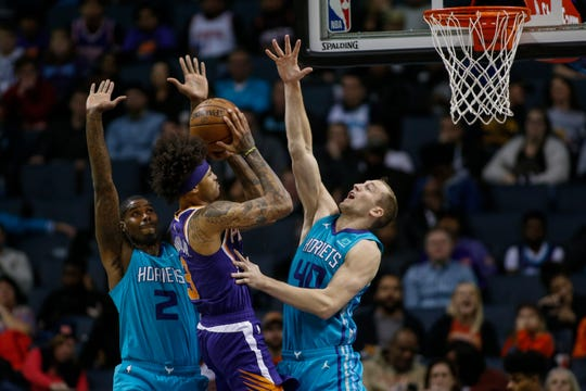 Phoenix Suns forward Kelly Oubre Jr., center, shoots over a double-team by Charlotte Hornets forwards Marvin Williams (2) and Cody Zeller (40) in the second half of an NBA basketball game in Charlotte, N.C., Monday, Dec. 2, 2019.