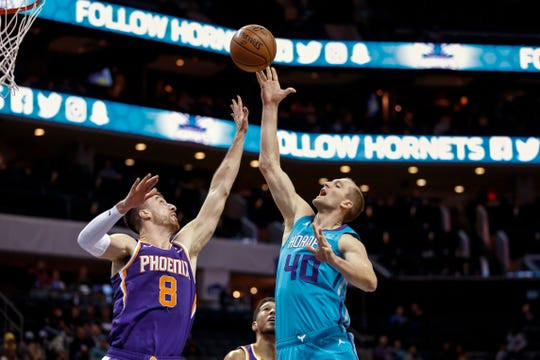 Charlotte Hornets forward Cody Zeller, right, shoots over Phoenix Suns forward Frank Kaminsky in the second half of an NBA basketball game in Charlotte, N.C., Monday, Dec. 2, 2019.