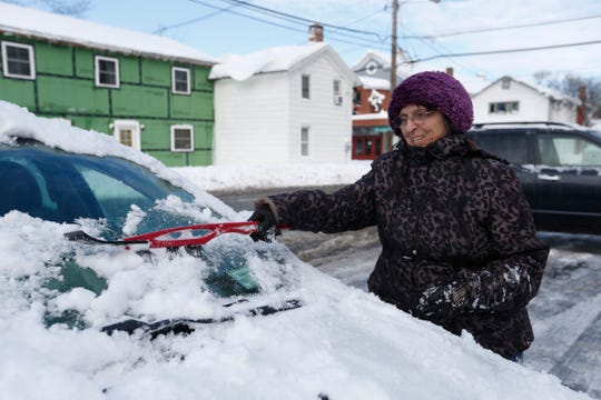 Suggy Moore, 84,  of Red Hook clears the snow from her car before starting her day on December 3, 2019.