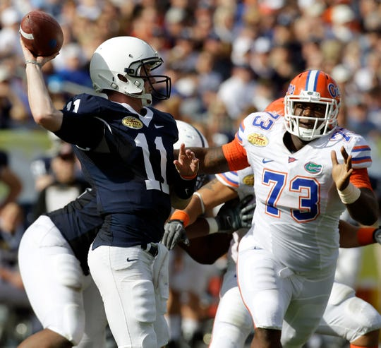Penn State quarterback Matt McGloin (11) throws a first half pass as Florida defensive tackle Sharrif Floyd (73) rushes during the Outback Bowl NCAA college football game Saturday, Jan. 1, 2011 in Tampa, Fla.  (AP Photo/Chris O'Meara)