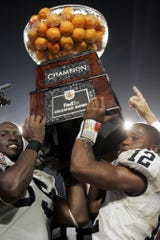 Penn State quarterback Michael Robinson (12), right, and Matthew Rice (55) lift the Orange Bowl trophy at Dolphins Stadium in Miami Tuesday Jan. 3, 2006. Penn State defeated Florida State 26-23 in triple overtime. (AP Photo/Carolyn Kaster)
