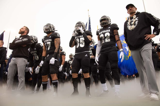Nevada head coach Jay Norvell, right, and his team prepare to take the field against UNLV on Saturday.