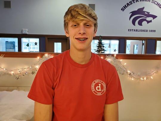 Shasta sophomore runner Dylan Jackson poses with holiday lights in the background inside his school's main office on Dec. 3, 2019 after an impressive showing at the CIF State Cross Country meet in Fresno on Nov 30.