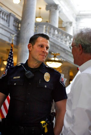 In this May 30, 2012, photo, Officer Kevin Peck of the West Valley Police Department, is congratulated after receiving the Law Enforcement Humanitarian Award at an awards ceremony honoring Utah's emergency responders at the Utah state Capitol, Salt Lake City. Peck was honored for calming and holding hands with a woman who was pinned underneath a UTA bus after getting hit while walking in a crosswalk in December 2011. The Deseret News reported that Peck helped save another crash victim while he was in Europe in November 2019. (Laura Seitz/The Deseret News via AP)