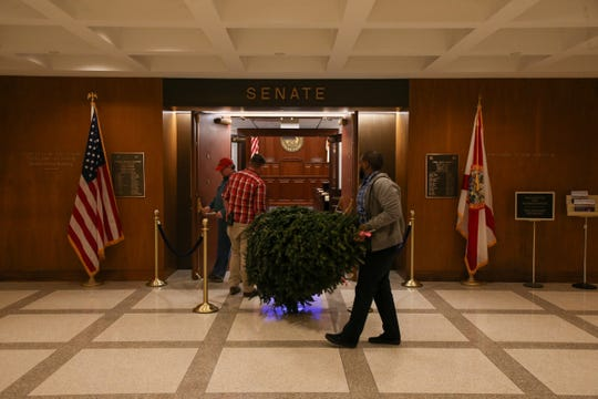 Jordan Richardson, left and Adam Reichert, both employees with the Sergeant of Arms office, carry the Senate Christmas tree from the elevator to the Senate chamber Tuesday, Dec. 3, 2019.