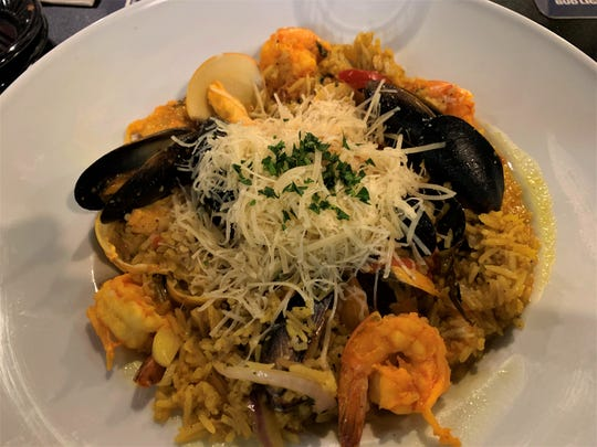 The Seafood Paella at Lola's Seafood Eaterystarred tender sweet clams, mussels, chicken, shrimp, and aromatic saffron-infused rice