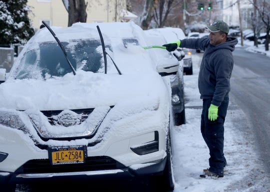 David Molgrovejo of Tarrytown clears snow from his car Dec. 3, 2019. A few inches of snow fell overnight, making a slow morning commute.